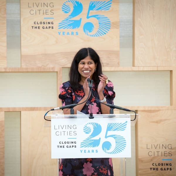 Lata Reddy smiles and applauds behind a podium at LC's 25th Anniversary.