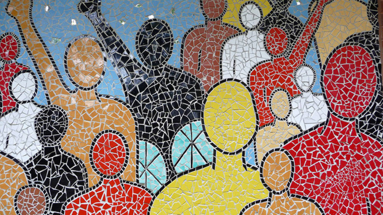 Mosaic artwork depicting colorful people, some with their arms raised in the air.