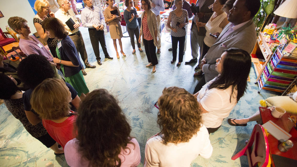 A group of people stand in a circle during one of The Integration Initiative Learning Communities.