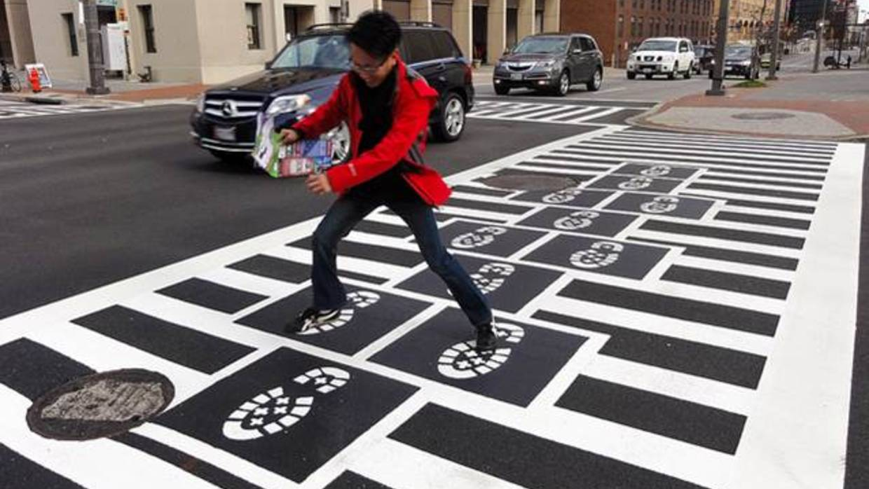 A man plays hopscotch across a playable crosswalk in Baltimore