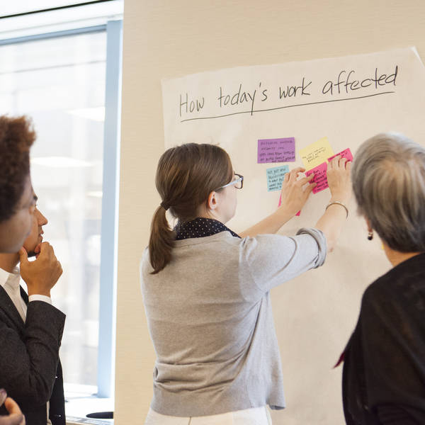 Participants in a TII Learning Community share notes on their day's work and lessons on a post-it board.