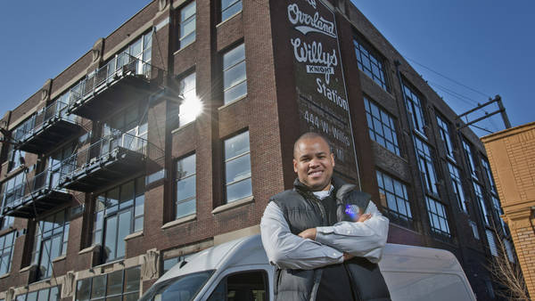 A young man stands in front of his employer's building in Detroit, MI