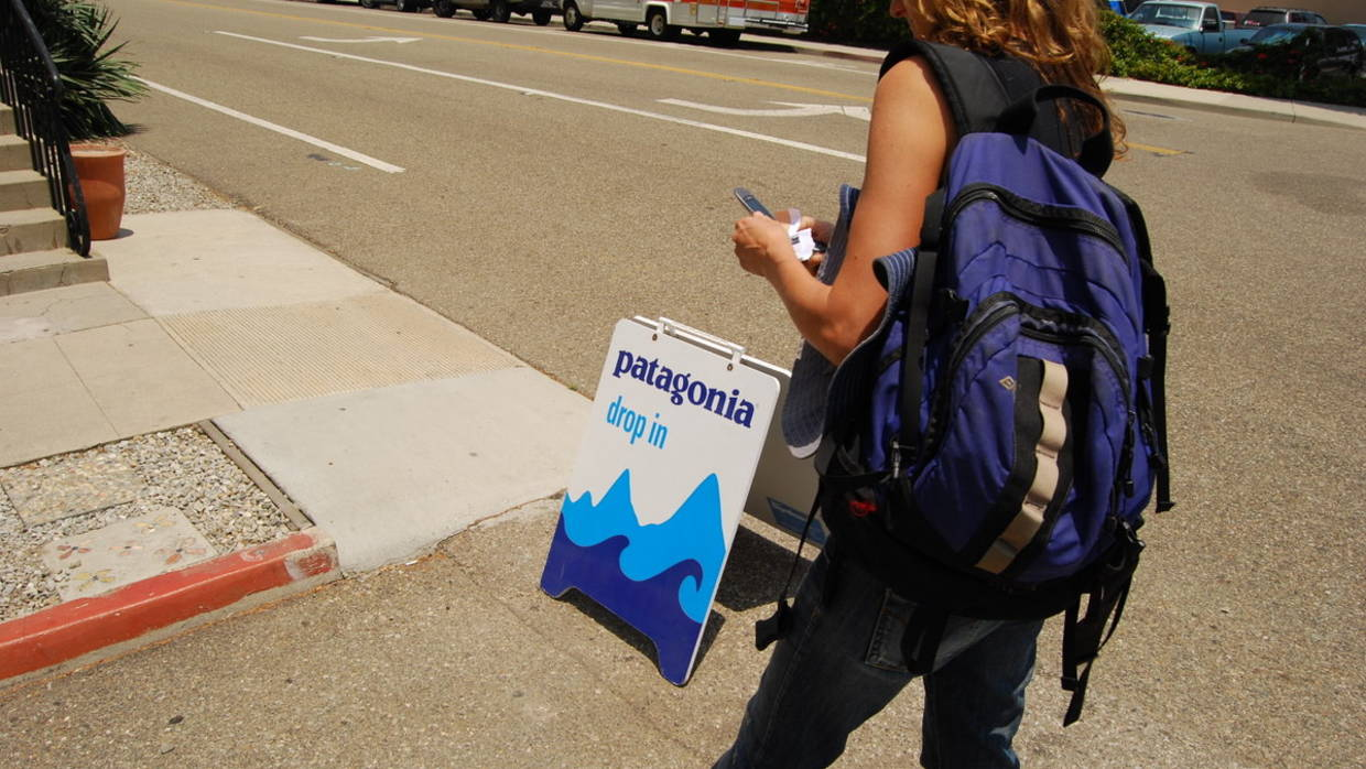 "A woman walks past a ""drop in"" sign before entering Patagonia athletic wear store."